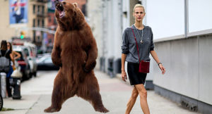 bear stands on hind legs and roars behind unsuspecting blonde woman